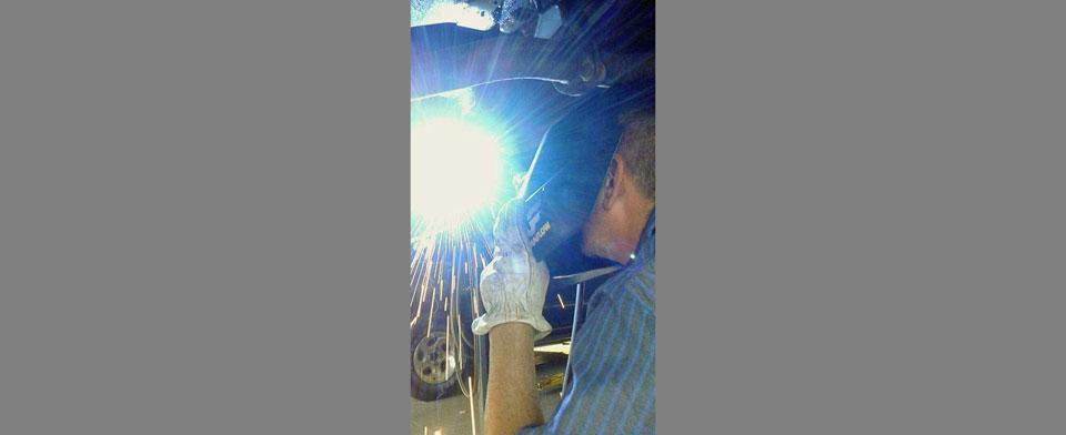 A welder working under a car