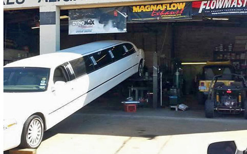Stretch limo with rear lifted for exhaust work