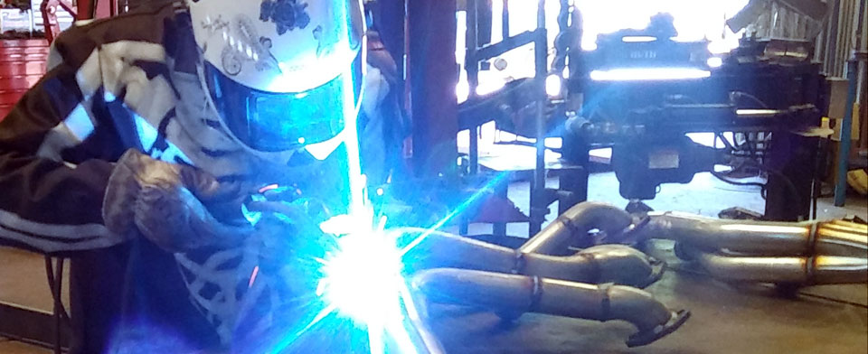 A welder fabricating a set of pipes